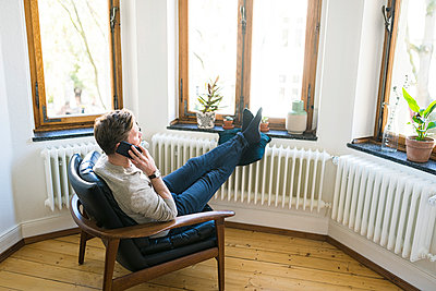 Casual man sitting in Lounge Chair in stylish apartment talking on the phone - p300m2083857 by Steve Brookland