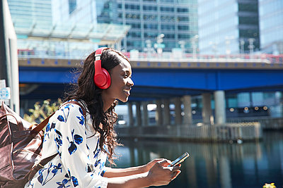 Smiling businesswoman with mobile phone and backpack looking away while standing in city - p300m2241632 by Pete Muller