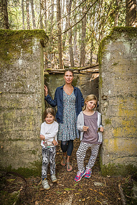 Woman and two daughters standing in derelict doorway in forest, Sandpoint, Idaho, USA - p429m2074434 by Alan Graf