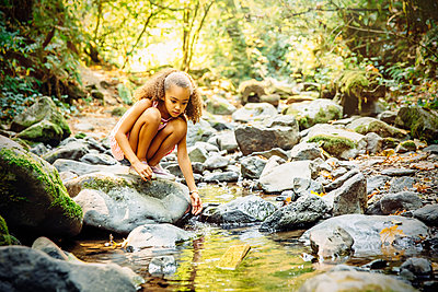 Mixed race girl exploring stream - p555m1306236 by Inti St Clair