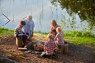Grandparents and grandchildren enjoying campfire at lakeside - p1023m1172710 by Francis Pictures