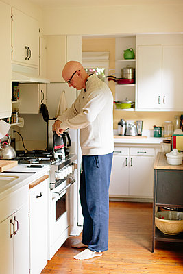 Man standing in a kitchen, making coffee. - p1100m1080231 by Mint Images