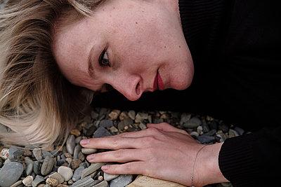 Woman lying on stones - p1363m2108766 by Valery Skurydin