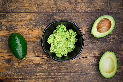 Bowl of Guacamole and whole and sliced avocados on dark wood - p300m1081438f by Larissa Veronesi