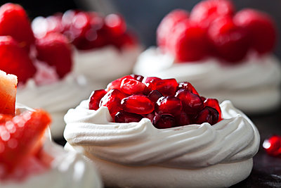 Meringue pastry garnished with whipped cream and pomegranate seed - p300m1587345 von Dieter Heinemann