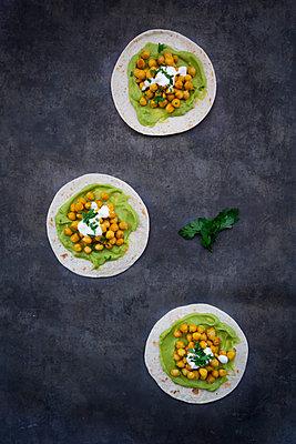 Pita-Brot mit Avocado-Creme, Kurkuma-Kichererbsen, Joghurt-Sauce und Petersilie - p300m2143998 von Larissa Veronesi