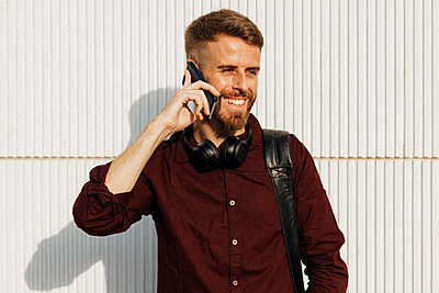 Businessman with shoulder bag smiling while talking on mobile phone standing against white wall - p300m2250373 by Boy photography