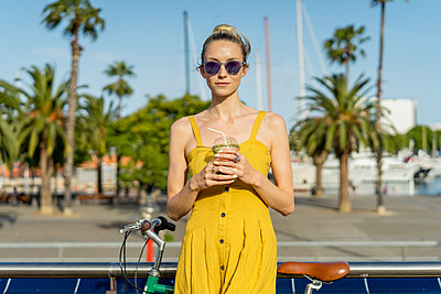 Beautiful woman with bicycle wearing sunglasses holding smoothie in city - p300m2287123 by VITTA GALLERY