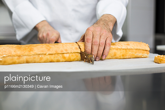 Chef cutting cake roll in portions - p1166m2130349 by Cavan Images