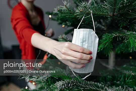 Woman's hand holding protective face mask hanged on Christmas tree at home - p300m2257021 by Oxana Guryanova