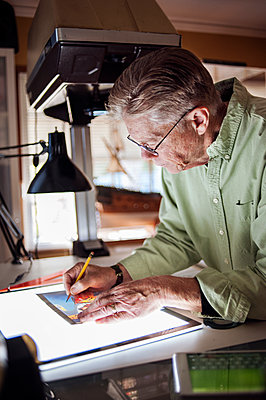 Senior man drawing on graphics tablet at home - p1166m1163150 by Cavan Images