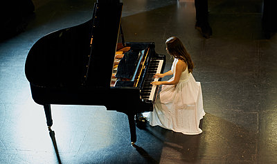 A woman with brown hair dressed in a white dress seen playing a black grand piano with the lid raised. View from above of the pianist - p1166m2152149 by Cavan Images