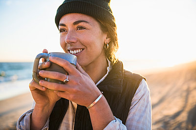 Young woman enjoying drink in mug while beach car camping alone - p1166m2285581 by Cavan Images