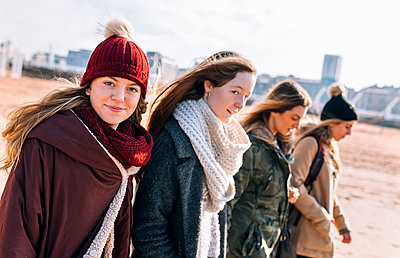 Portrait of teenage girl walking on the beach with her friends in winter - p300m1228372 by Marco Govel
