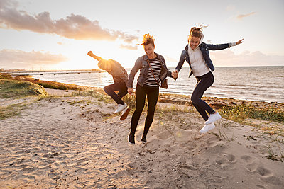 Smiling mother and children jumping at beach during weekend - p426m2205285 by Kentaroo Tryman