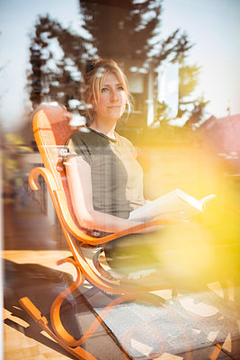 Young woman reading a book in a rocking chair at home - p741m2176776 by Christof Mattes