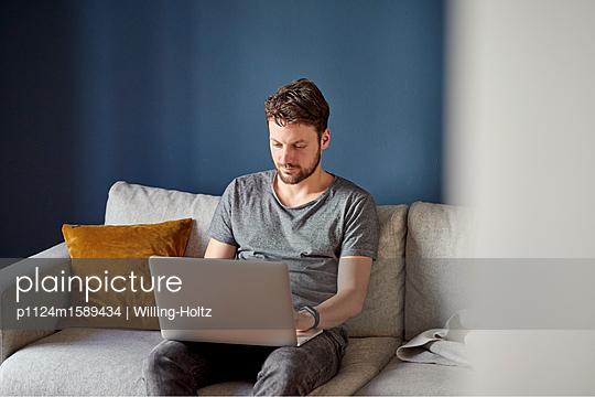 Junger Mann arbeitet am Laptop Computer - p1124m1589434 von Willing-Holtz