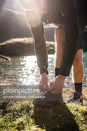 Wanderer bindet sich die Schuhe an Bergsee - p1142m2056632 von Runar Lind