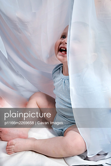 baby girl hiding behind curtains - p1166m2269658 by Cavan Images