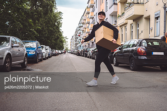 Low angle view of delivery woman with cardboard box walking on street in city - p426m2205372 by Maskot