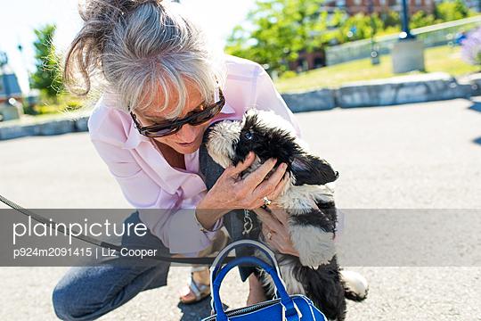 Senior woman petting cute dog in park - p924m2091415 by Liz Cooper