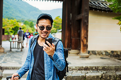 A man in sunglasses looking at his smart phone.  - p1100m1185878 by Mint Images