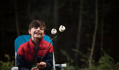 Happy boy looking at roasted marshmallows on a metal stick. - p1166m2214651 by Cavan Images