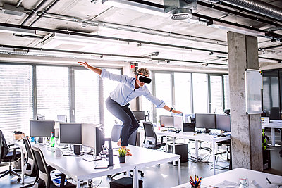 Barefoot mature businessman on desk in office wearing VR glasses - p300m1568087 von HalfPoint