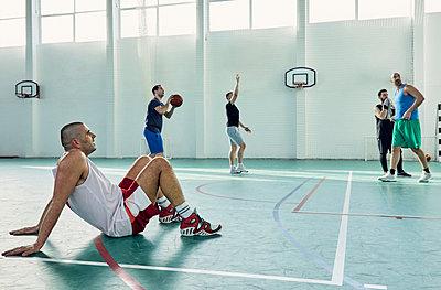 Basketball player sitting on court - p300m1588105 von Zeljko Dangubic