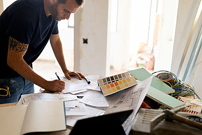Man working on construction plan and colour swatch - p300m2207119 by Valentina Barreto