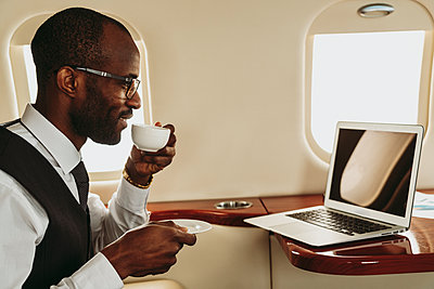 Businessman drinking coffee while working on laptop in airplane - p300m2257053 by OneInchPunch