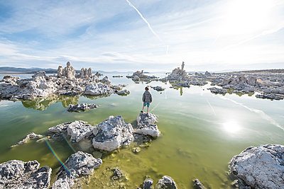 Rear view of boy standing on Mono Lake rocks in front of tufa towers, California, USA - p343m1490633 by Alasdair Turner / Aurora Photos