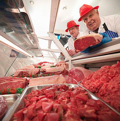 Butcher examining meat in case - p42914668f by Monty Rakusen