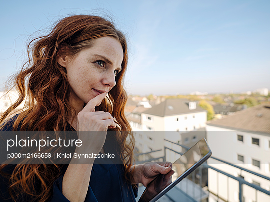 Redheaded woman with tablet on rooftop terrace - p300m2166659 by Kniel Synnatzschke