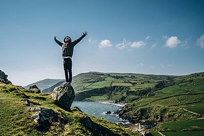 Carefree man standing on rock overlooking sunny, idyllic landscape, Northern Ireland - p1023m2067636 by Anna Wiewiora
