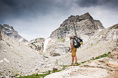 A backpacker stops to take in a view of the mountains.  - p343m1184710 by Rob Hammer