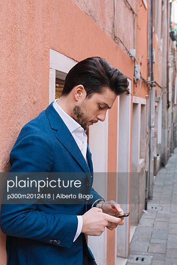 Businessman using smartphone in the city - p300m2012418 von Alberto Bogo