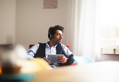 Portrait of pensive man with headphones and tablet sitting on armchair looking out of window - p300m1562813 by Sigrid Gombert