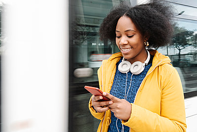 Young woman text messaging on smart phone while standing by tram - p300m2266404 by COROIMAGE