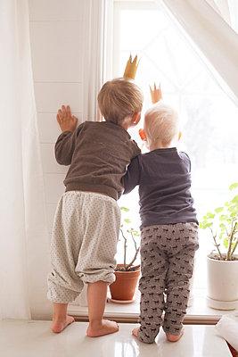 Boys wearing paper crowns looking through window - p312m1024562f by Wenblad-Nuhma