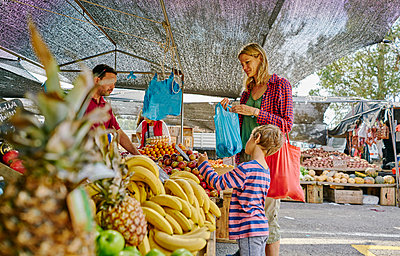 Mother and sons shopping at fruit and veg stall at market, Montevideo, Uruguay, South America - p429m1519598 by Stephen Lux