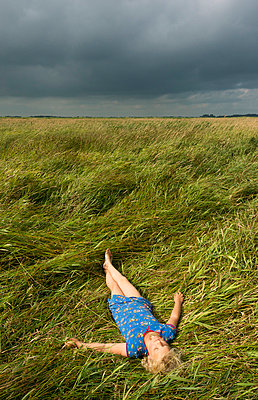 Girl relaxing in field of tall grass - p429m711773f by Mischa Keijser