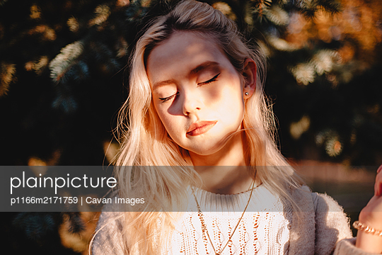 Portrait of young woman with eyes closed standing in front of sunlight - p1166m2171759 by Cavan Images