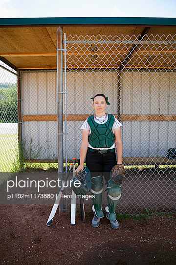 Portrait serious middle school girl softball catcher at dugout fence