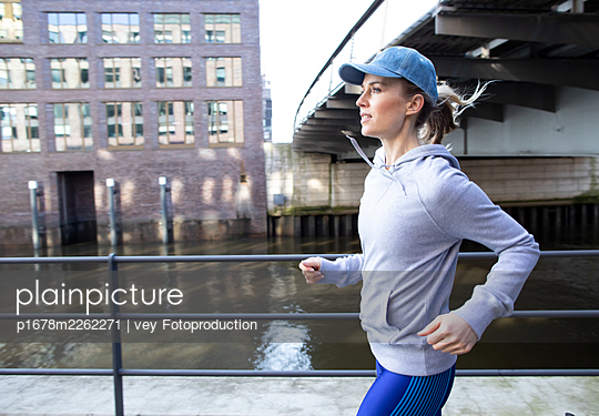 Woman jogging in Hamburg - p1678m2262271 by vey Fotoproduction