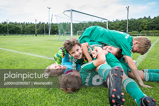 Germany, young football players lying on top of each other - p300m2090567 von Westend61