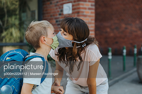 Mother kissing son wearing protective face mask standing in font of school - p300m2226112 by Mareen Fischinger
