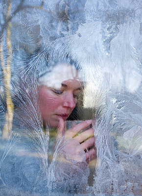 Woman drinking a hot drink behind a window covered with frost flowers - p1231m1043092 by Iris Loonen