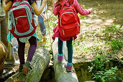 Girls with backpacks balancing on logs in forest - p300m1588014 von Zeljko Dangubic