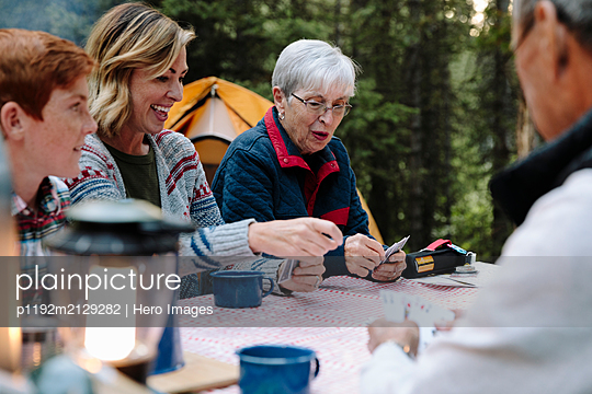 Multi-generation family playing cards at campsite picnic table - p1192m2129282 by Hero Images